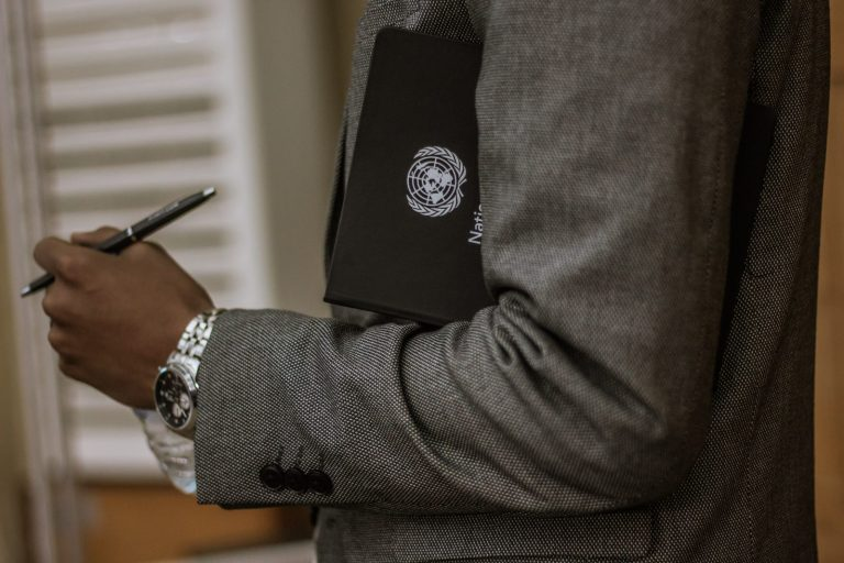 man holding black book and pen